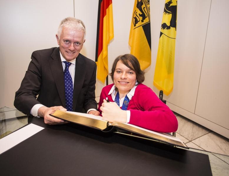 Medaillengewinnerin Anja Wicker trägt sich ins Goldene Buch der Stadt Stuttgart ein (v.l.n.r. OB Fritz Kuhn, Anja Wicker) Foto: Leif Piechowski/Stadt Stuttgart